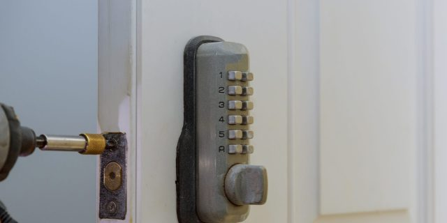 Electronic door handle installed on wood door with digital door lock systems security protection for apartment.