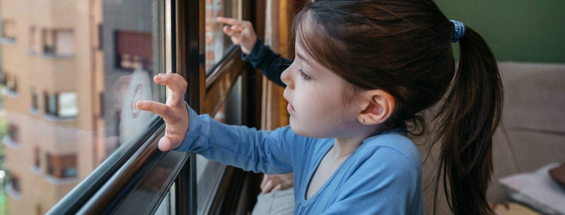 Two children in coronavirus lockdown playing draw on the window glass
